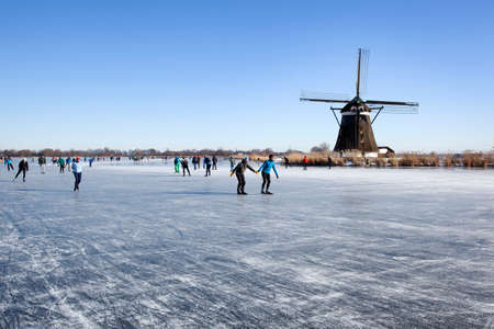 Zevenhuizen, Netherlands - February 13, 2021: Dutch winter landscape with Ice skaters on the Rottemeren near a windmill Redactioneel