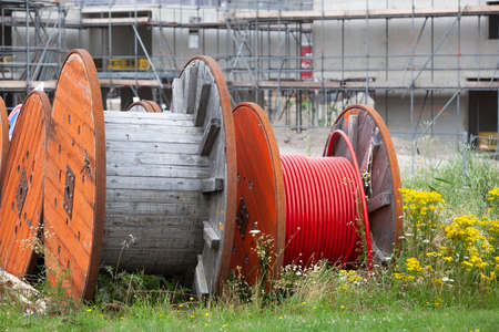 Huge spools with cables for the construction industry to connect new built houses Stock Photo