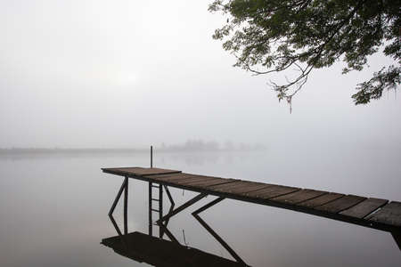 Jetty in the misty river Meuse in Geijsteren in the North of Limburg