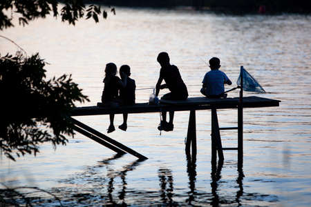 Silhouette of children fishing in the river Meuse from a jetty in Geijsteren in the North of Limburg