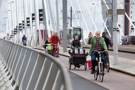 Rotterdam, Netherlands – September 13, 2021: : Cyclists and a tram on the Erasmus bridge in Rotterdam