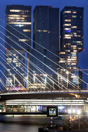 Rotterdam, Netherlands – September 15, 2021: Urban twilight view of the Erasmus bridge in Rotterdam and the building De Rotterdam by architect Rem Koolhaas.