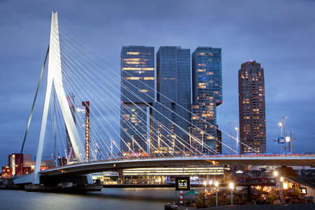 Rotterdam, Netherlands – September 15, 2021: Urban twilight view of the Erasmus bridge in Rotterdam with the building De Rotterdam by architect Rem Koolhaas in the background Editorial