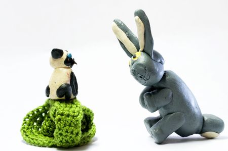 Clay Kitten on knitted basket and gray rabbit photo