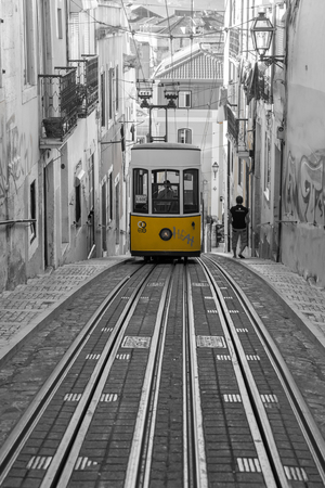 Lisbon, Portugal - October 30, 2016: Famous Bica Funicular. The Elevador or Ascensor da Bica is a popular tourist attraction in Chiado District, Lisbon. Tagus river on background. Editorial