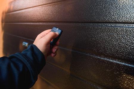 ガレージドアPVC。ガレージドアを閉めて開くためのリモコンを手で使用します。 写真素材