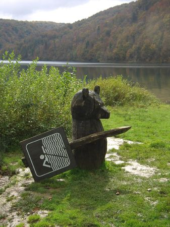 exacting: an exacting wooden bear at a lake, Plitvice