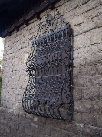 grating: old-type patterned wrought iron grating on window covered by folding shutters, Tata
