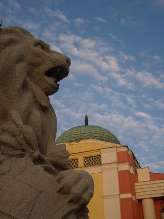 culumn of lion in front of a coloured building, Mohacs, Hungary