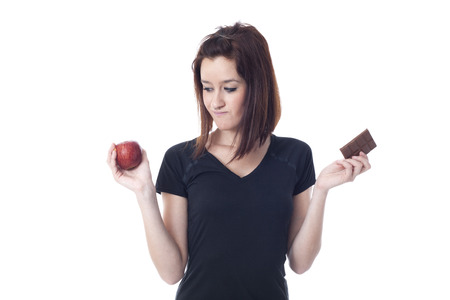 Young worried woman torn between a chocolate bar and fresh apple isolated on white photo