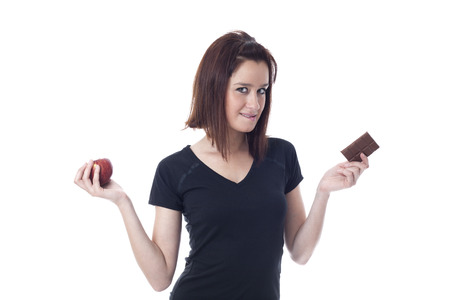 guilty pleasures: Young woman biting down on the lips torn between a chocolate bar and fresh apple