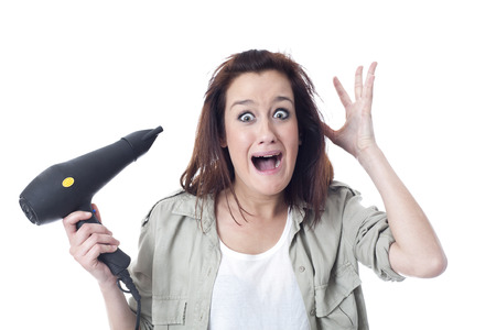 Stressed woman holding hair dryer photo
