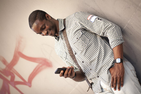 Young black man checking messages on his smart phone photo