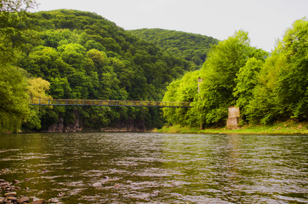 The river on the background of green forest and old suspension bridge. photo
