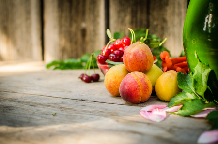 summer fruits: Still life of summer fruits. orange peaches, red cherries and green leaves of the tree. against the background of a wooden texture