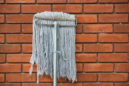 dirty mop against the orange brick wall  photo
