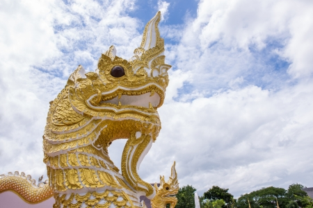 golden naga in Temple of Thailand against blue sky photo