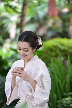 Beautiful girl is in garden and drinking  tea photo