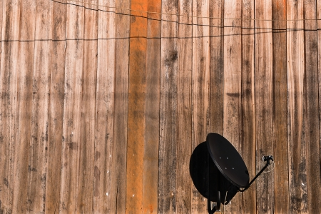 Satellite Dishe against with wooden wall photo