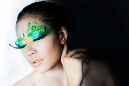 beautiful women with perfect art make up and long false eyelashes made from feathers