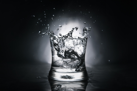 ice cube splashing into a glass full of water photo
