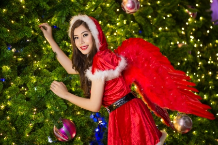 Pretty Asian girl in Santa costume for Christmas with night light photo