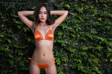 Sexy girl in shiny orange bikini photo
