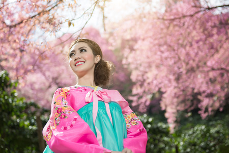 Hanbok: the traditional Korean dress and beautiful Asian girl with sakura photo
