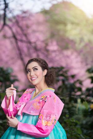 Hanbok: the traditional Korean dress and beautiful Asian girl with sakura photo
