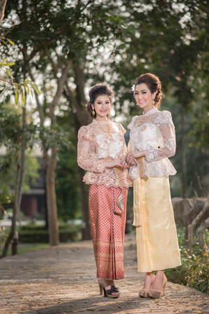 Two beautiful girls getting dressed in Thai Traditional Costume