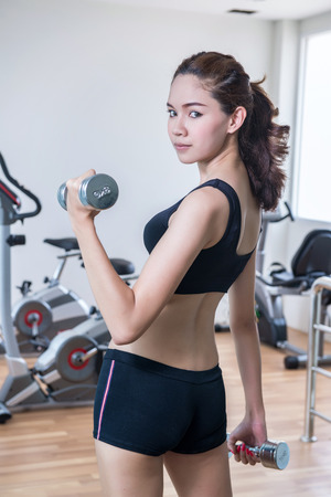 young fit woman lifting dumbbells photo
