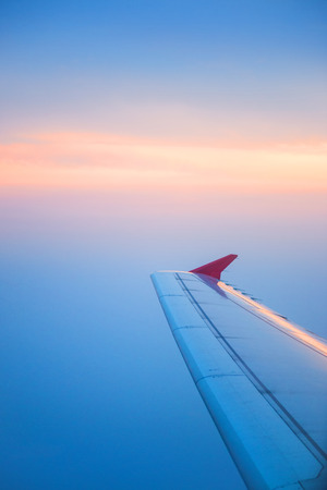 airplane window: Wing of an airplane flying in the sky Stock Photo