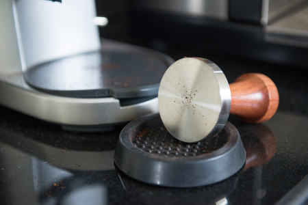 tamper: offee tamper and roasted coffee in rubber base Stock Photo