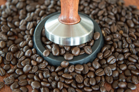 tamper: coffee tamper and roasted coffee in rubber base