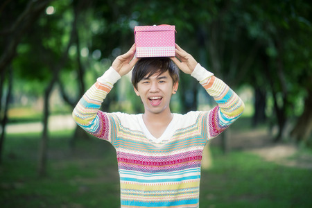 Male is holding a pink gift box photo