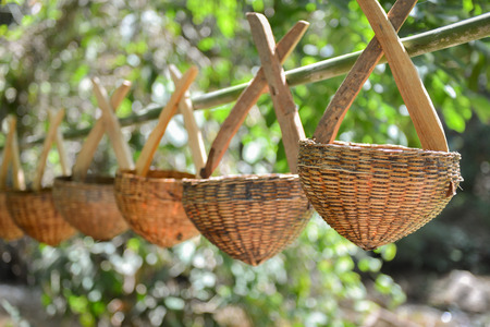 wickerwork: Rattan basket hanging on bamboo stick Stock Photo