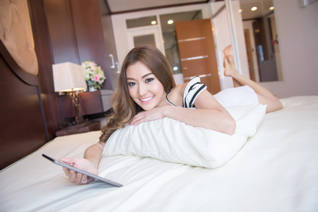 Young beautiful woman playing tablet photo