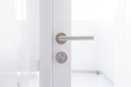 Detail of a metallic knob on white door