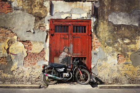 PENANG, MALAYSIA-JUL 18, 2014  General view of a mural  Boy on a Bike  painted by Ernest Zacharevic in Penang on July 6, 2013