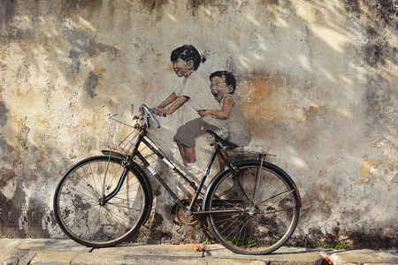 PENANG, MALAYSIA - JUL 18, 2014   Street Mural entitled  LIttle Children on a Bicycle  painted by Ernest Zacharevic in Penang on June 15, 2013