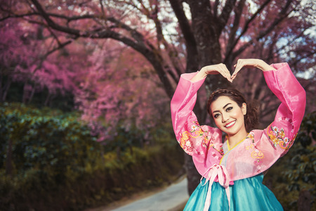 Hanbok  the traditional Korean dress and beautiful Asian girl with sakura photo