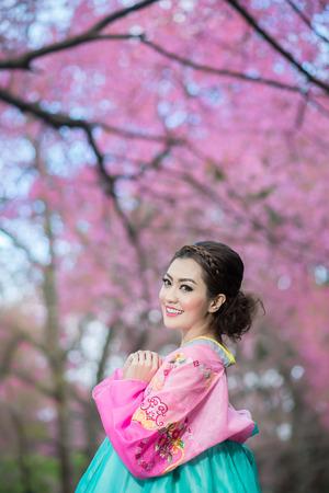 Hanbok  the traditional Korean dress and beautiful Asian girl with sakura Archivio Fotografico
