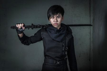 assassinate: Asian man dresses as Ninja holding sword Stock Photo