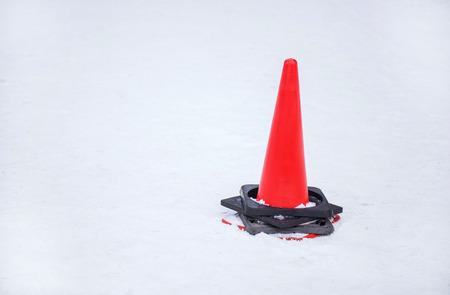 traffic cone: traffic cone at a sidewalk on snow