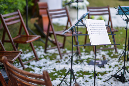 orchestration: Music stand and empty chairs in the garden Editorial
