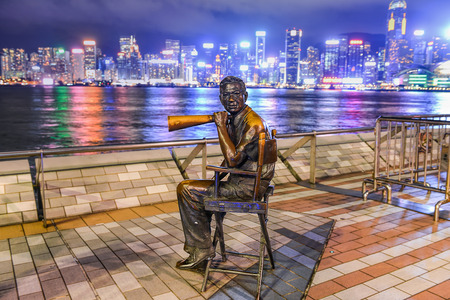 honours: HONG KONG, CHINA - JUNE 09: Statue and skyline in Avenue of Stars on JUNE 09, 2015 in Hong Kong, China. The promenade honours celebrities of the Hong Kong film industry as the famous attraction. Editorial