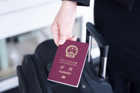 Hand holding China passport, ready to travel