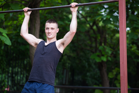 pullups: strong man doing pull-ups on a bar outdoor