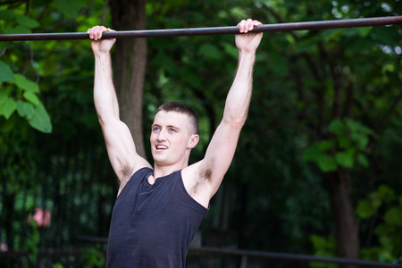strong man doing pull-ups on a bar outdoor