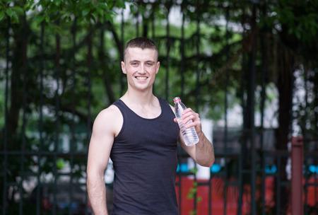 man drinking water: Handsome athlete man drinking water
